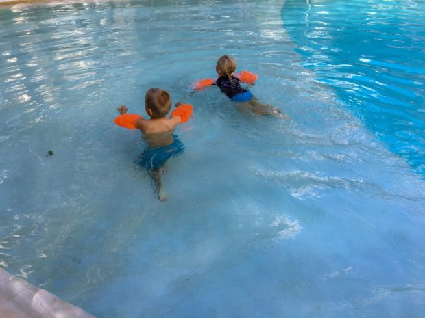 two kids wearing orange arm floaties, swim in a turquoise pool. best sunblock for babies best sunscreen for toddlers