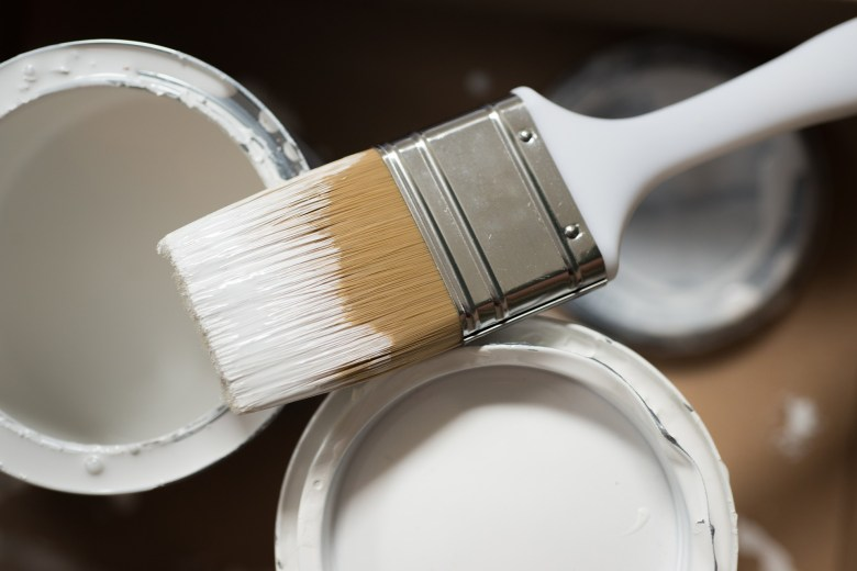 Household paintbrush balanced over two tins of white paint