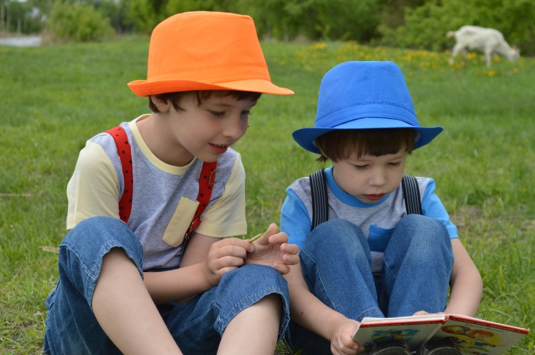 two young boys reading a book outside