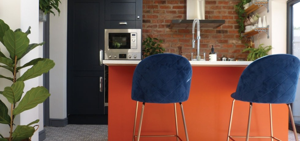 Bright orange kitchen island with blue chairs