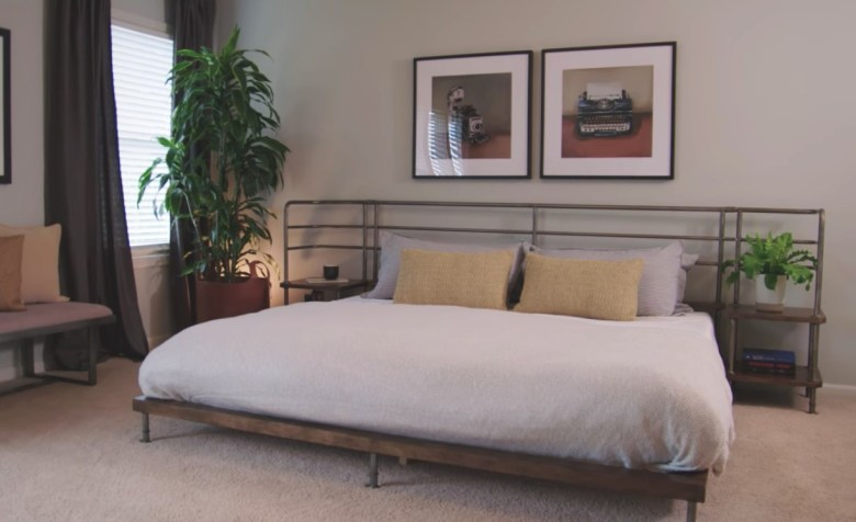 Low bed with plants on bedside table and yellow pillows