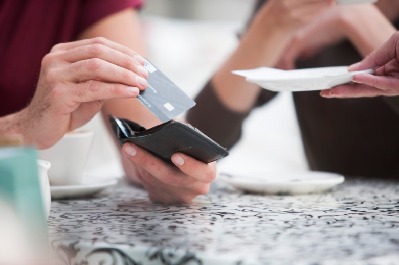 Man takes credit card from wallet to place on plate