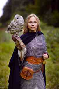 girl in chain mail holding owl in forest.