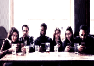 Six people sit around a table in a pub with nearly finished pint glasses in front of them. All are looking intently at their smartphones