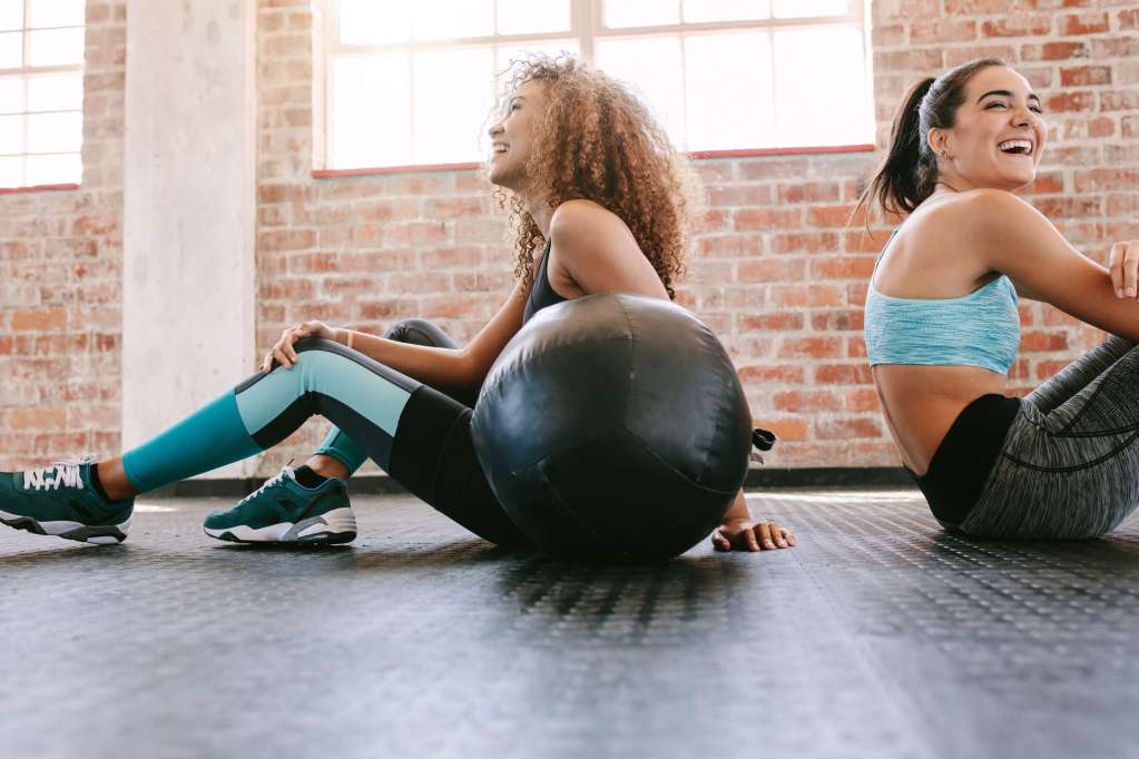Happy young female friends sitting on gym floor with medicine ball and smiling. Two young women taking a break from workout. Web Design for Wellpreneurs.