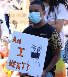 """Young Black boy holds a sign that reads """"Am I Next?"""" while at a BLM rally in London."""