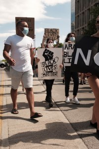 """Protesters in London, ON holding signs that read """"Black Lives Matter""""."""