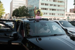 A young Black girl stands out of a car sunroof with her fist raised in the air.