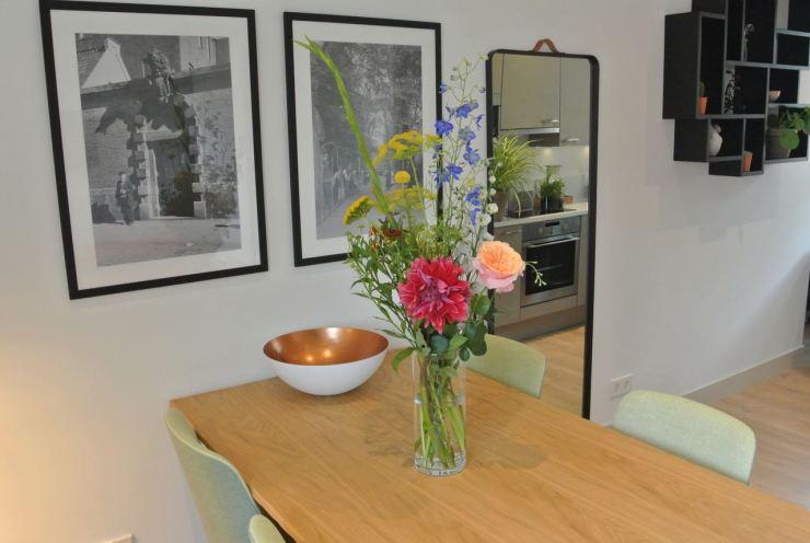 Klein boeket met bloemen op de eettafel in hotelkamer.