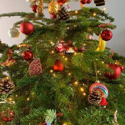 Versierde kerstboom met rode kerstballen, dennenappels en figuurtjes.