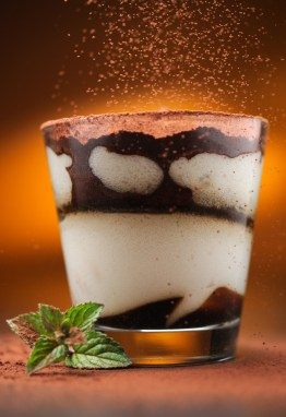 Pouring cacao powder to tiramisu in glass