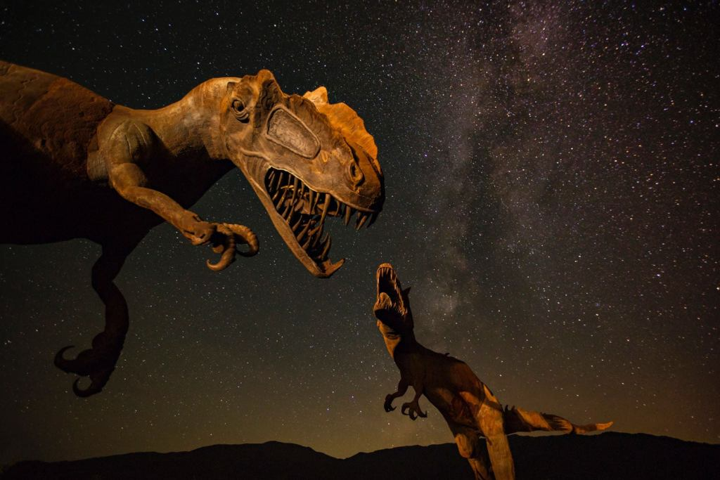 Dinosaur Sculptures at Night with stars in the background