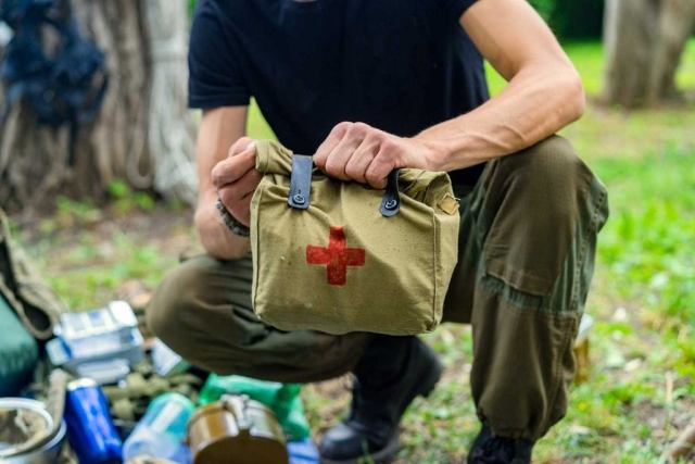 Person outdoors holding a first aid kit.