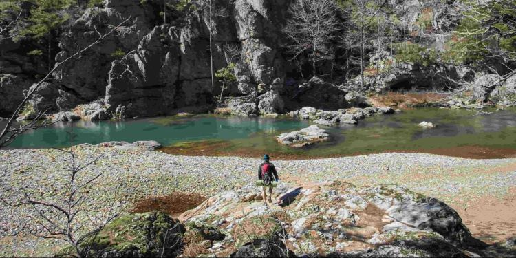 Man in front of rock face in Ouachita National Forest