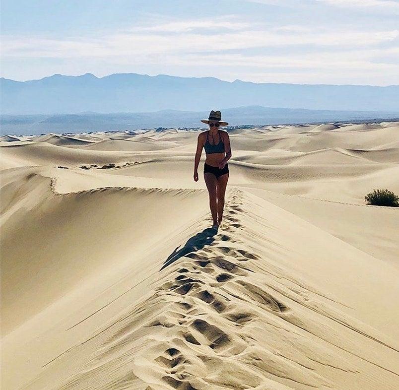 a woman walks on a california desert dune