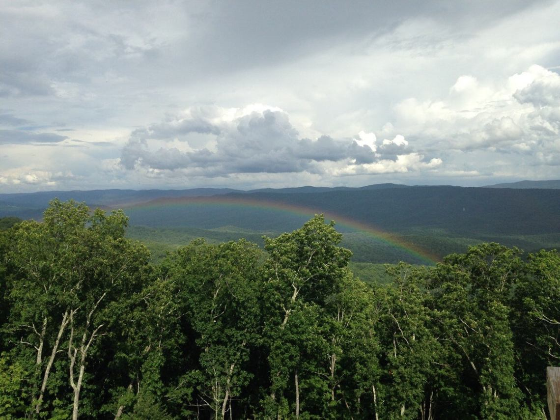 view of a rainbow over the trees taken from greenbrier valley hiking trail
