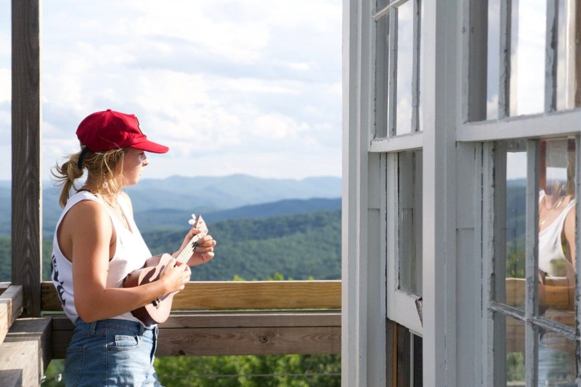 woman in a red hat and white tank top plays a ukulele on the fire tower porch