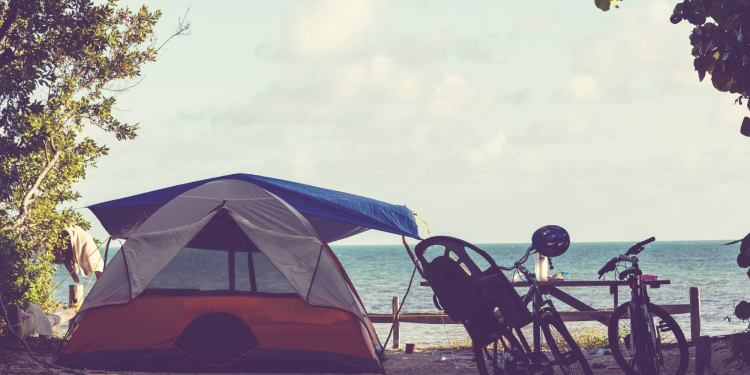 a tent and bicycle rest on a sandy myrtle beach campground