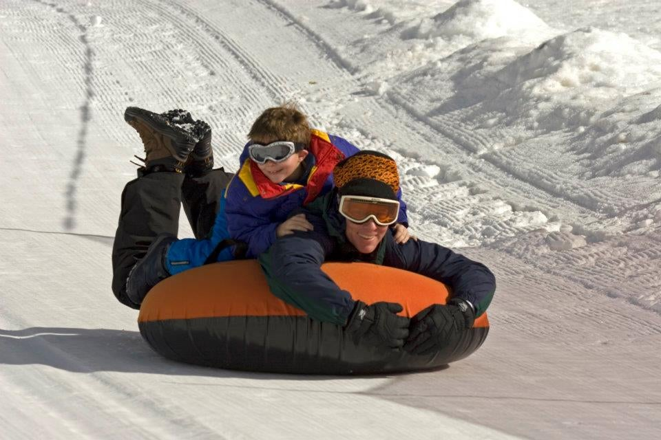 father and son smiling on snow tube