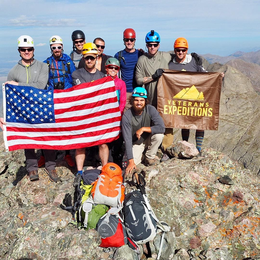 group of veterans on a rocky mountain summit with american flag and veteran expeditions f;ag