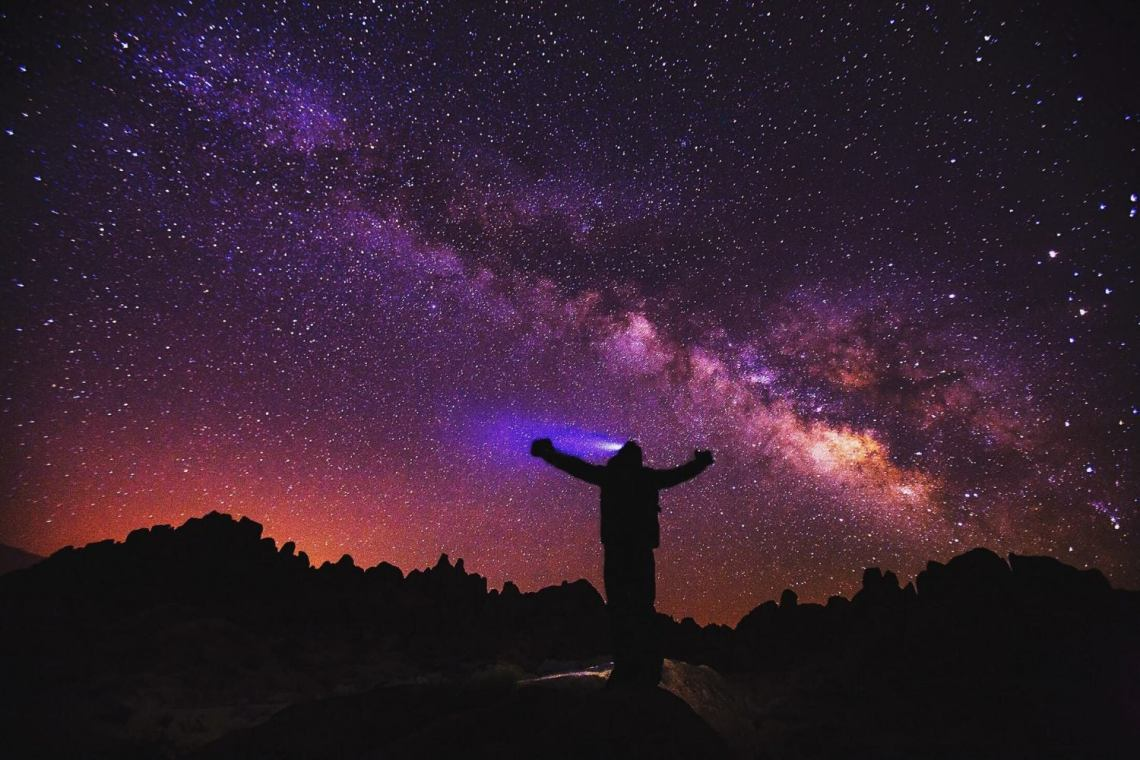 silhouette of a hiker wearing a headlamp as milky way is seen above in the purple and pink night sky