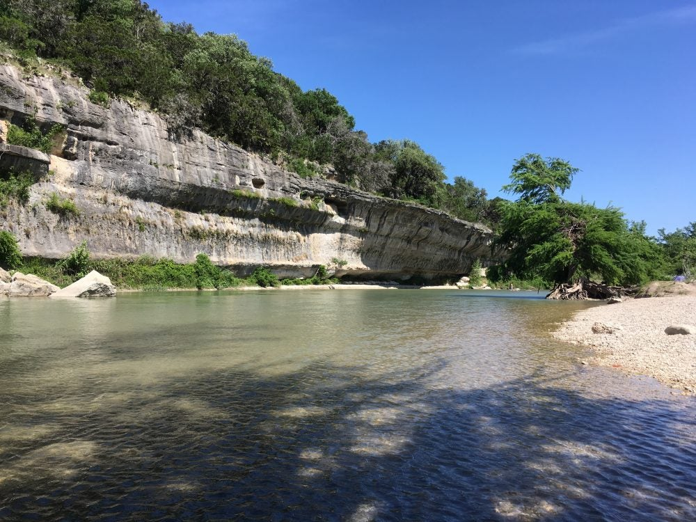 A beach and rock wall along the Guadalupe River in Texas