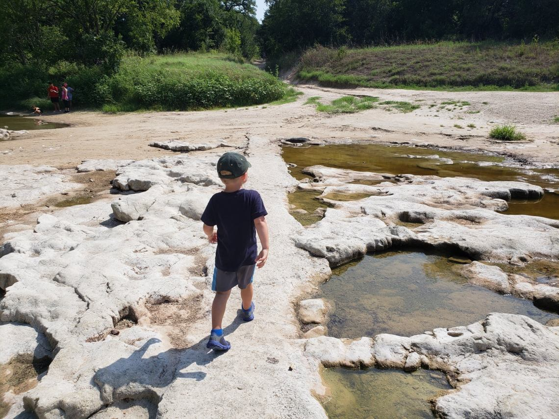 Child walking in Dinosaur park among fossils