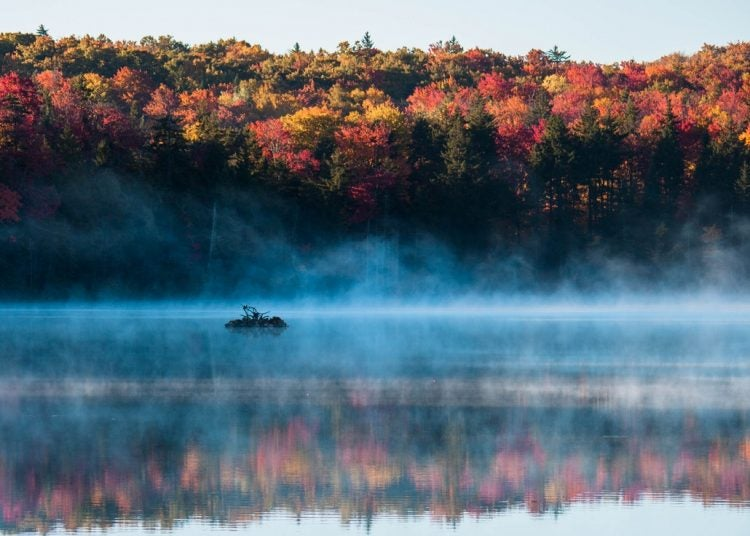 Early morning fog dissapates on a still lake in Woodfors State Park