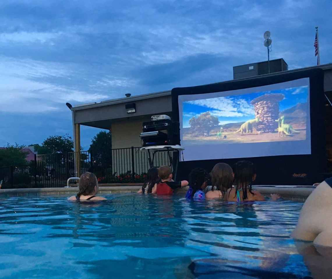 kids in a pool watching outdoor movie screen at the Nashville KOA
