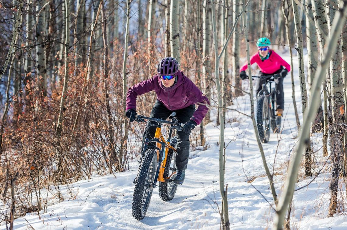 Two female cyclists hunched over their handle bars as they ride through trees on fat bikes in winter