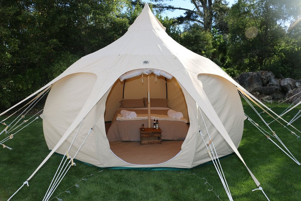 lotus belle glamping tent set up with furnishings in a lush field
