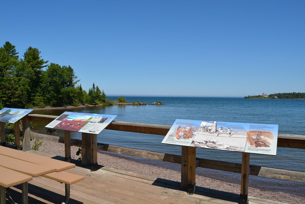 lake view beside benches and infographic signs.