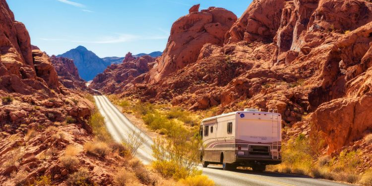 rv driving down road in a red rock canyon