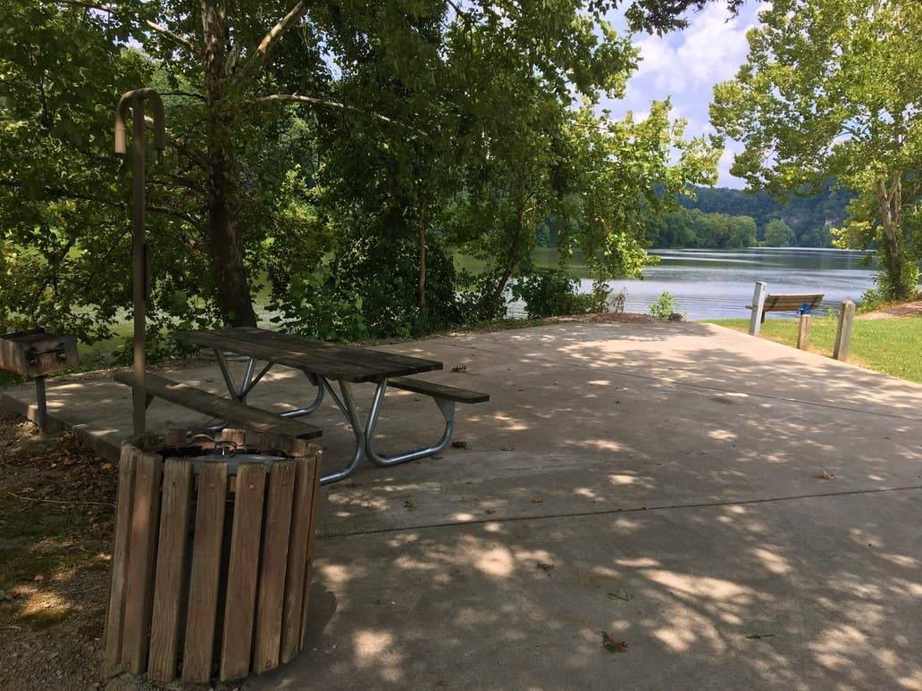 picnic table on concrete slab at Campsite with river access at Harpeth River Bridge Campground