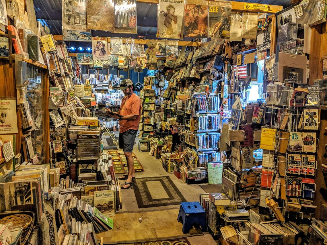 The interior of a book store in Quartzsite, AZ, with a man reading a book