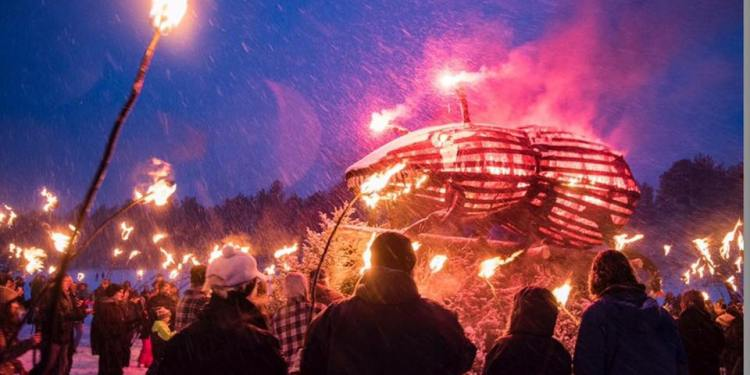 a wooden beetle burning in south dakota in front of a large crowd