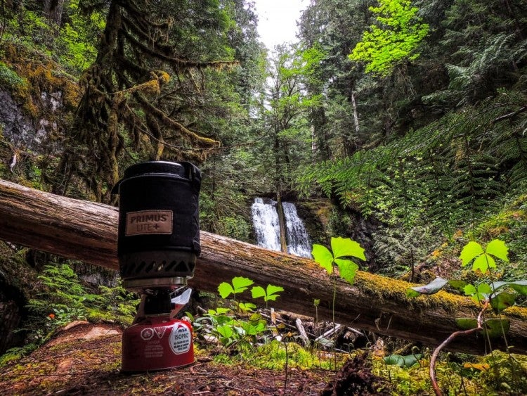 small primus backpacking stove in front of waterfall in mossy forest