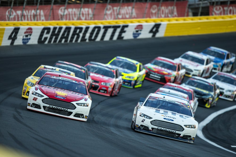 Several multicolored race cars on Charlotte's angled home track