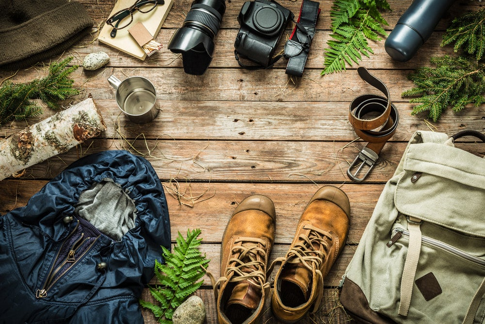 rustic gear arranged on wooden table showcasing hiking boots, camera and backpack