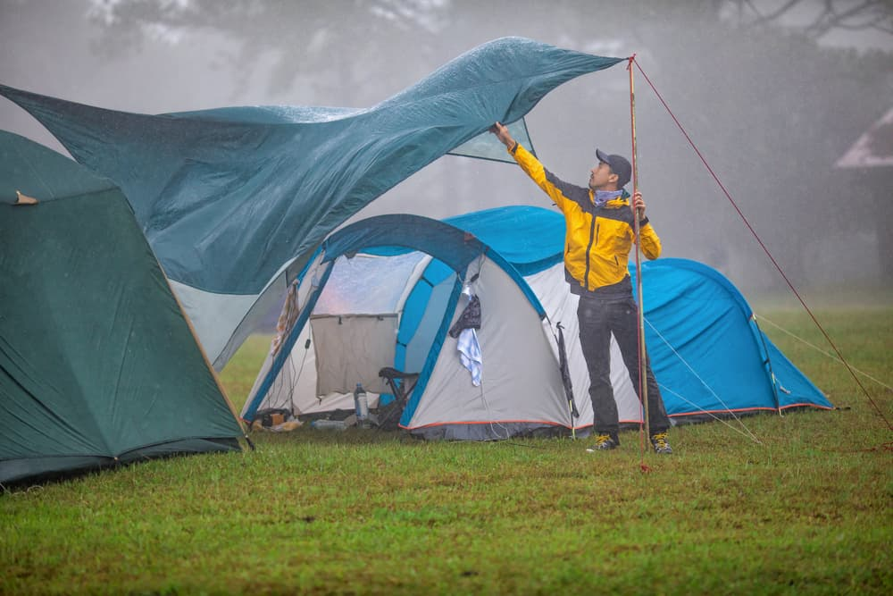 camper tries to set up tarp between two tents during windy rainstorm