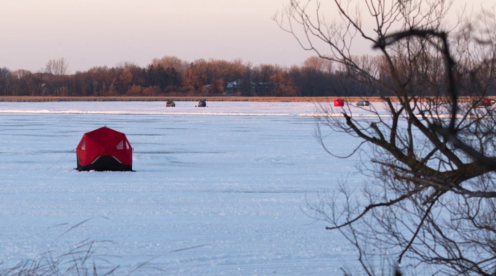 a single red ice fishing tent sits on a frozen lake in minnesota with multiple ice fishing tents behind it