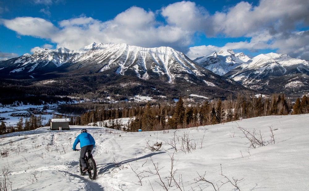 Person in winter gear riding a fat bike through a snow field towards a mountain range