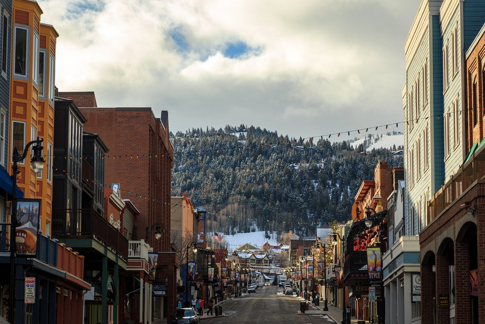 A street in downtown Park City Utah with colorful christmas lights strung in front of a snowy mountain
