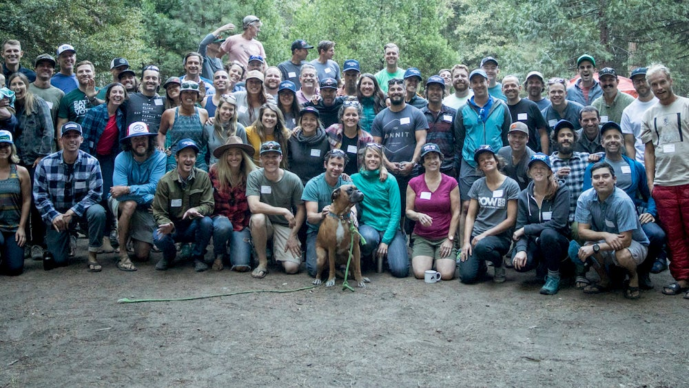 a large group of Protect Our Winters employees and a dog posing for a photo