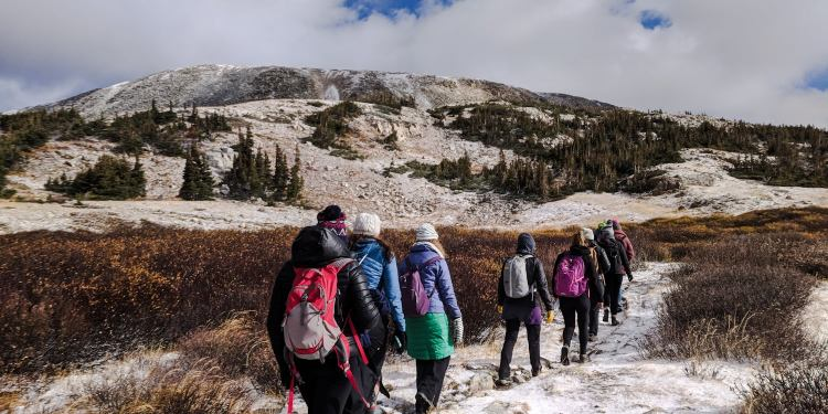 Women hiking while bundled in puffer jackets and beanies with day packs, headed up a trail through snow in Wyoming.