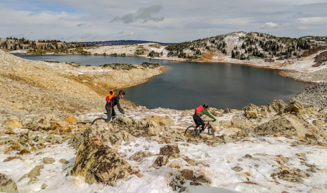 Two mountain bikers manuever through rugged landscape and snow patches beside an alpine lake.