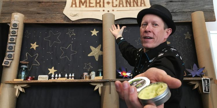 man posing for photo holding americanna cbd cream in front of sales booth