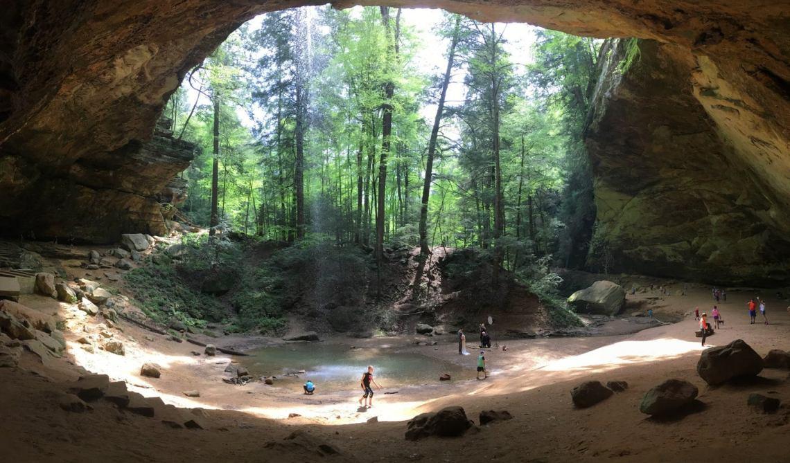 People walking below the waterfall inside Old Man's Cave.