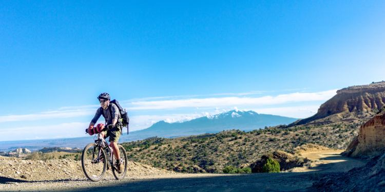 Man biking along trail with mountains in background