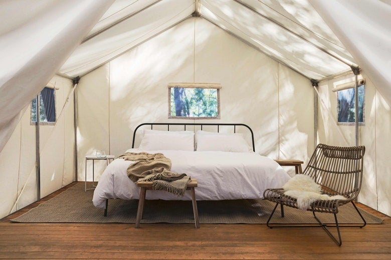 white bedding covers large bed inside of canvas glamping tent, featuring modern furniture and furs